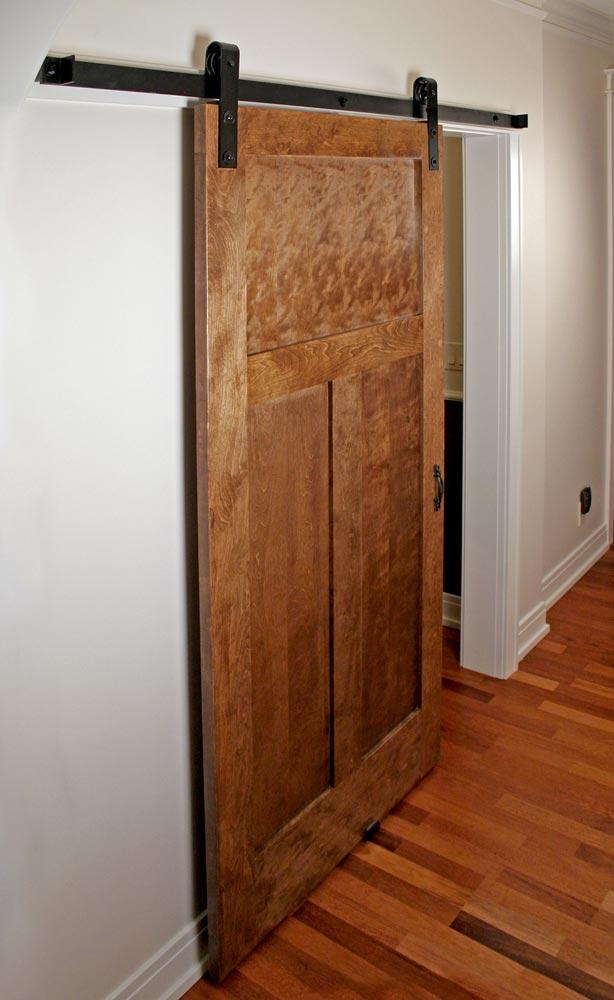 Closet entry with flat track hardware on sliding Craftsman style door.
