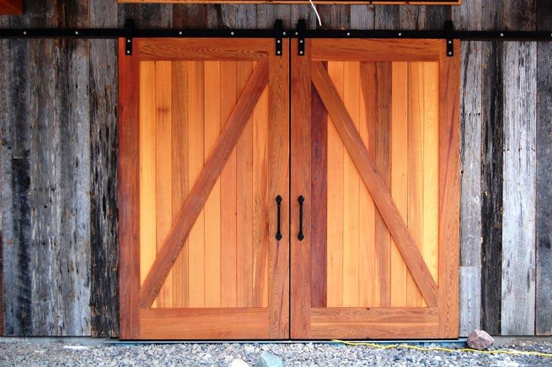 Rustic sliding garage doors with flat track hardware.