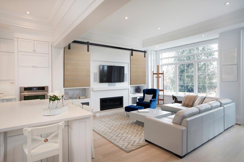 Flat track hardware on double sliding door conceals living room TV monitor.